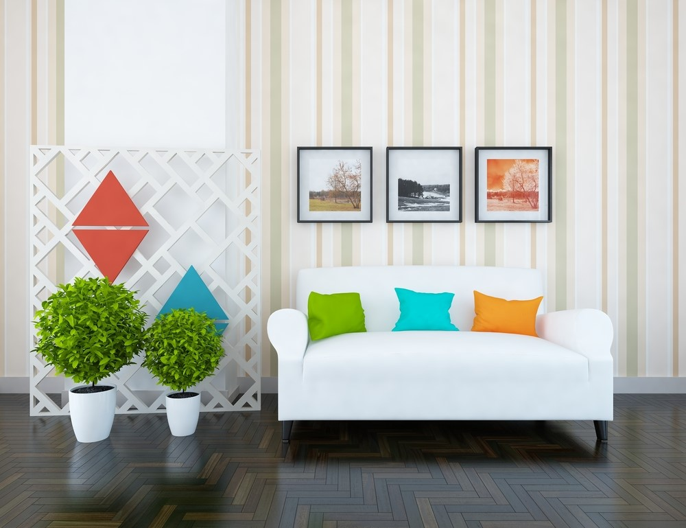 Pillows in solid colors complement the more complex art and plants adjacent to them.